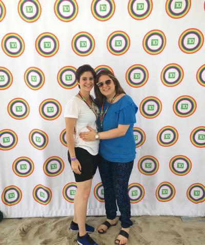 Christina Papadimitriou at the Long Beach PRIDE Parade with her girlfriend; Shows two women smiling, standing against photo backdrop