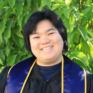 A chest up photo of Shirley. They are wearing their blue and gold Berkeley undergraduate stoll. They are smiling at the camera at a 3/4 face view, pointing to the left. The background consists of bright green tree leaves.