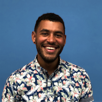 a picture of a smiling man with brown skin and a floral shirt