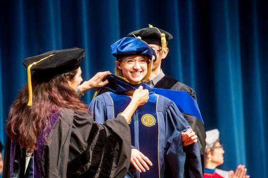 Ph.D. alumna Elaine Sedenberg is hooded by her faculty advisors (Noah Berger Photography)