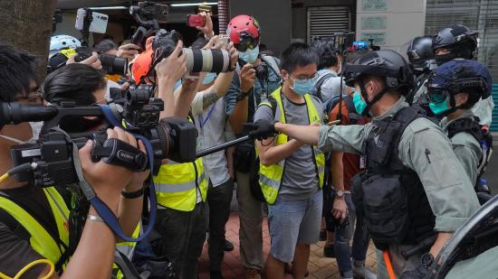 Riot police clear away media gathered in Hong Kong last week ahead of debate on a bill that would criminalize abuse of the Chinese national anthem. (Vincent Yu/AP via NPR)
