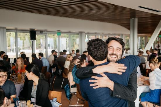 classmates hug at a reception