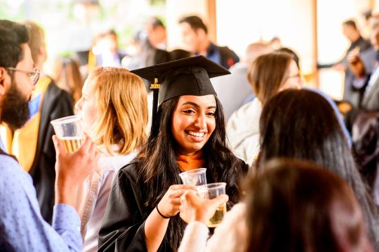 graduate clinks champagne with friends after the ceremony