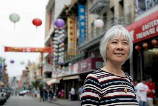 photo of Judy Yung standing in front of a street in San Francisco Chinatown