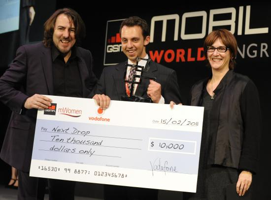 Ari Olmos (center) accepts the award from event host Jonathan Ross & Lee Epting of Vodafone