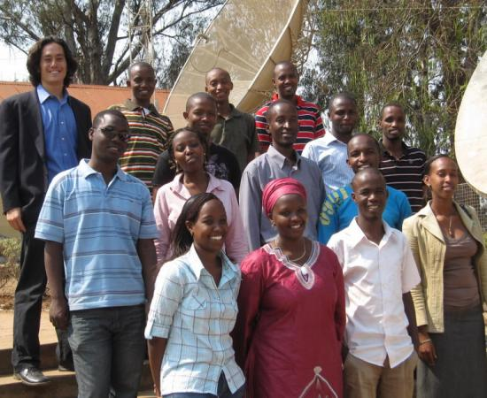 Josh Blumenstock (left) with 14 Rwandan university students who have assisted with his research.