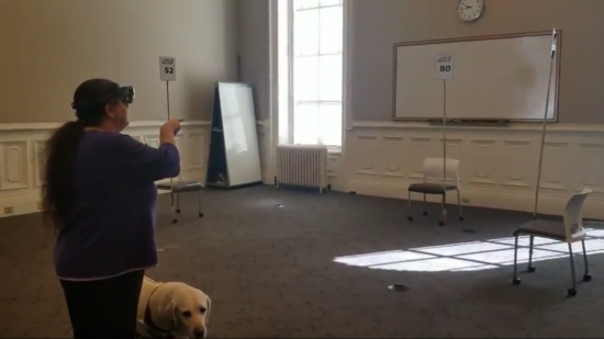 A blind test user wearing an AR device points towards a bus stop